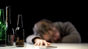male alcoholic passed out with three empty beer bottles surrounding him